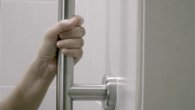 Woman holding on handrail in toilet.