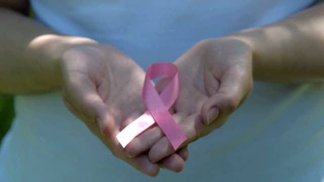 woman holding pink awareness ribbon in hands - breast cancer awareness filmów i materiałów b-roll