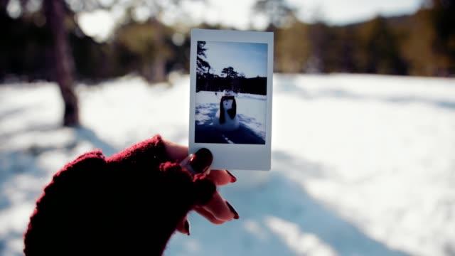 stockvideo's en b-roll-footage met vrouw met polaroid foto van sneeuwpop in besneeuwde bergbos - polaroid