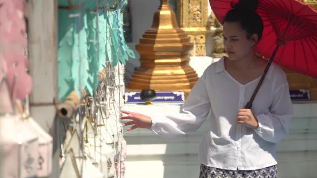 frau hält roten regenschirm mit blick auf dekoration vor dem tempel - dekorative kunst stock-videos und b-roll-filmmaterial
