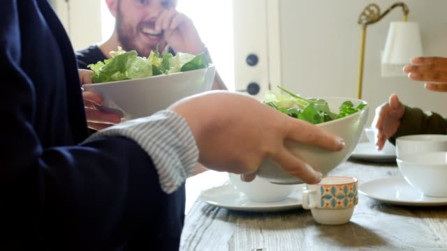 Woman holding salad bowls walks toward dining table and serves food to friends video