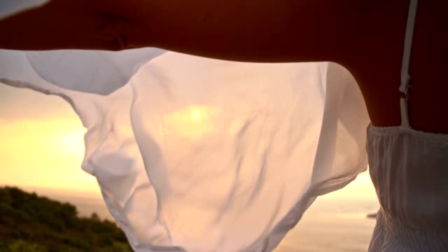 SLO MO Woman holding shawl in wind on a coast video