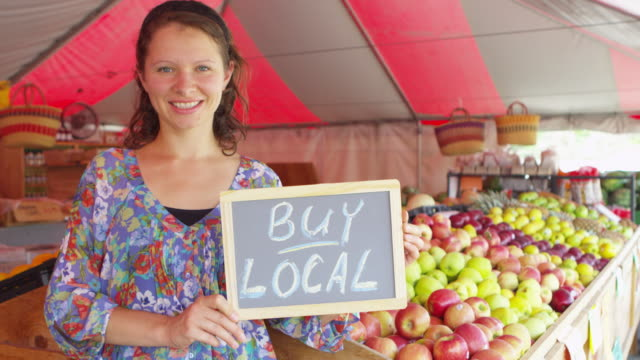 Woman holding sign saying buy local from fruits market video