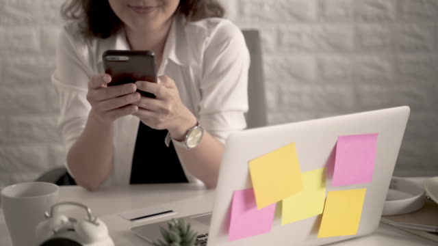 Woman holding smart phone and using laptop computer video