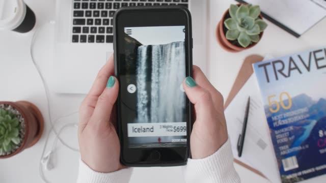 frau mit smartphone betrachten pauschalreisen - eine reservierung vornehmen stock-videos und b-roll-filmmaterial