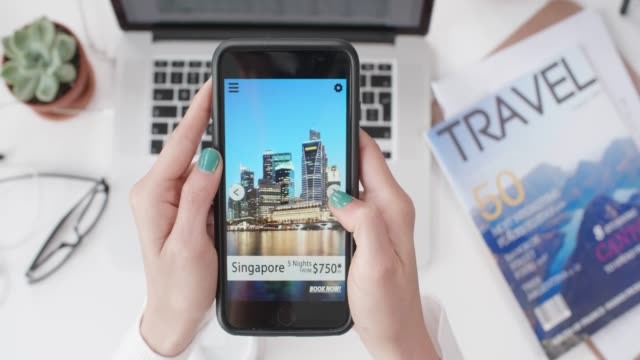 woman holding smartphone looking at travel packages - fare una prenotazione video stock e b–roll