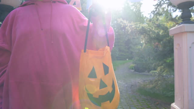 Woman holding Trick or Treat bag, asking for sweets at Halloween party entrance