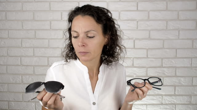 Woman holding two types of glasses. Woman holding two types of glasses. In one hand pinhole in other regular glasses for bad eyesight. eye chart stock videos & royalty-free footage
