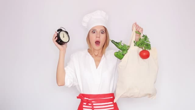 woman holding with different vegetables and vintage clock video