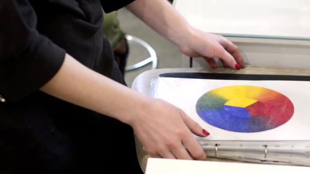 Woman holds a color wheel wheel in her hands in creative office. Female make-up artist teaches the techniques of make-up on a masterclass. video