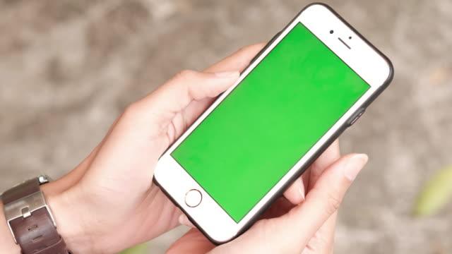 kadın bir yeşil scren akıllı telefon tutar - hand holding phone stok videoları ve detay görüntü çekimi