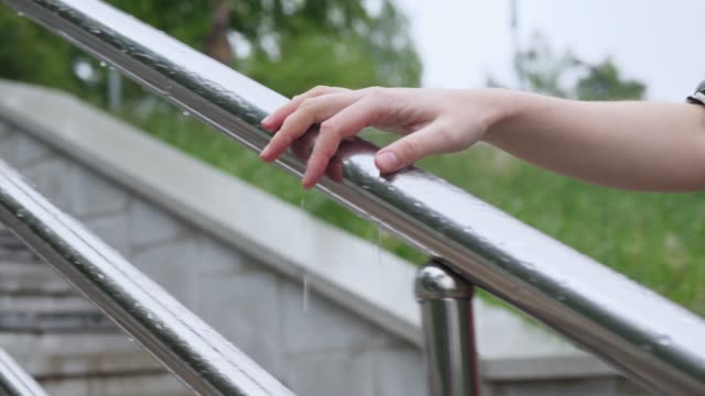 Woman holds hand on wet metal railing, water drops dripping down her fingers. video