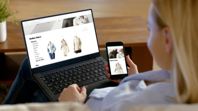 Woman Holds Smartphone and Has Laptop on Her Knees, Browses Online Store that Sales Fashionable Clothes.