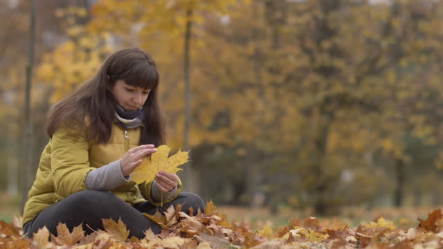 woman holds yellow maple leaf in hands in autumn thinking about something, slow motion