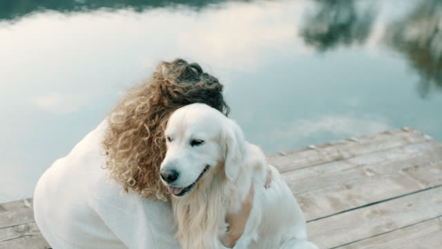 Woman hugging retriever dog Young woman hugging retriever dog on pier on lake locs hairstyle stock videos & royalty-free footage