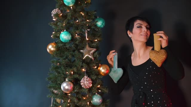 A woman in a black dress decorates the Christmas tree with Christmas toys.