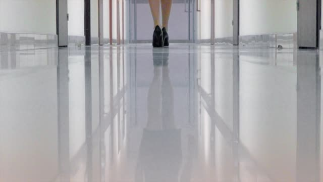 woman in a black high heeled shoes walking away in the corridor of office building - high heels stock videos & royalty-free footage
