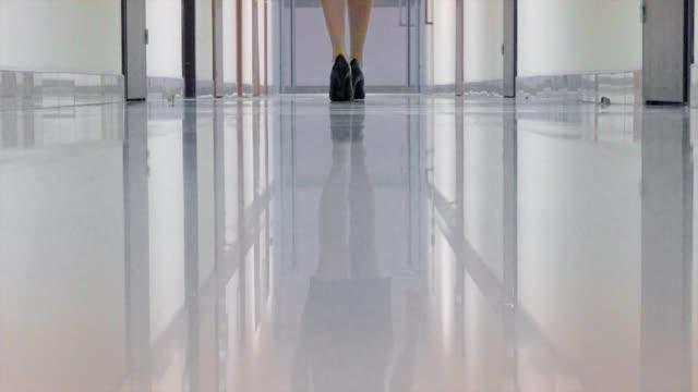 vídeos de stock, filmes e b-roll de sapatos de mulher de um negro alto salto distância andando no corredor do prédio de escritórios - salto alto