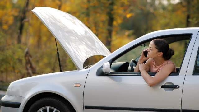 vídeos de stock e filmes b-roll de woman in a broken car talking by the phone - berma da estrada