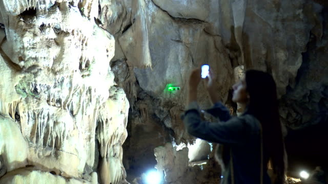 Woman in a Cave taking photos video