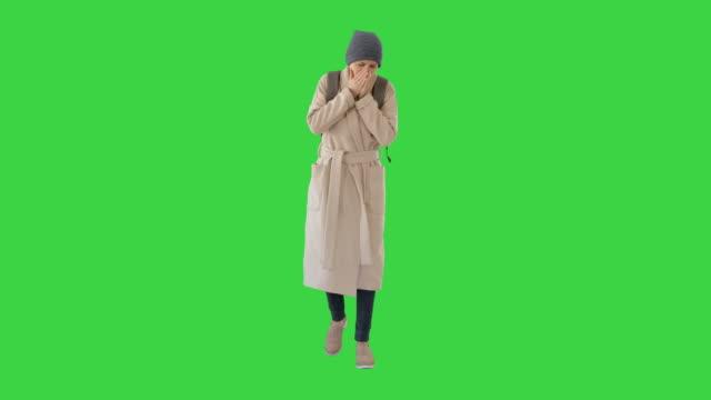 vídeos y material grabado en eventos de stock de mujer con un abrigo caminando y tosiendo en una pantalla verde, chroma key - abrigo