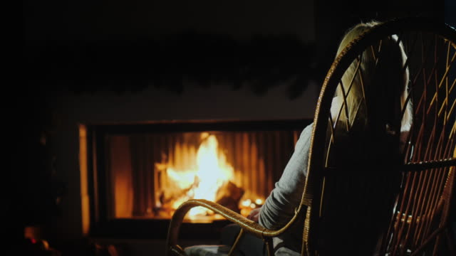 A woman in a comfortable rocking chair is resting by the fireplace in the twilight A woman in a comfortable rocking chair is resting by the fireplace in the twilight. rocking chair stock videos & royalty-free footage