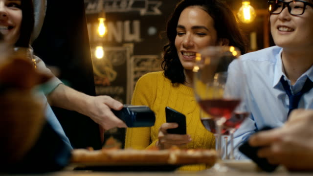 vídeos de stock e filmes b-roll de woman in a company of friends pays for her order with a contactless mobile phone payment. young people have fun and joke around. - paying with card contactless