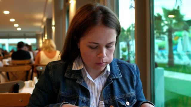 vidéos et rushes de une femme dans une veste en denim mangeant dans un restaurant, elle tient un couteau et une fourchette. - fourchette