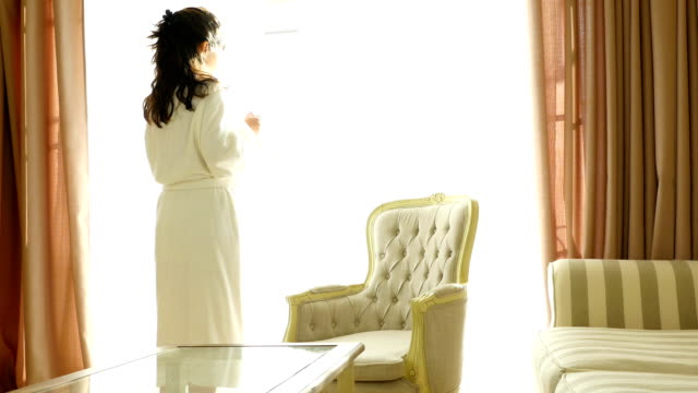 Woman in a dressing gown sipping her morning coffee by the window and looking outside video