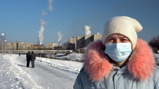 a woman in a face mask against the background of smoking pipes in a winter. - abiti pesanti video stock e b–roll