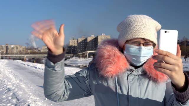 vidéos et rushes de une femme dans un masque dans le contexte des pipes de tabagisme en un hiver. - photophone