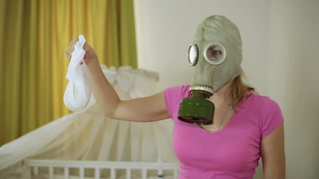 A woman in a gas mask looks disgustedly at the children's diaper A woman in a gas mask looks disgustedly at the children's diaper disgust stock videos & royalty-free footage