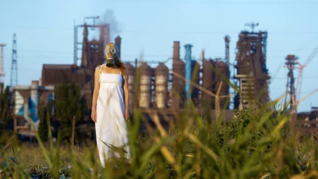 vídeos y material grabado en eventos de stock de mujer en una máscara de gas en un fondo de tubos de humo de una fábrica - apocalipsis
