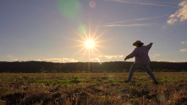 a woman in a hat rides on the field - cowboy video stock e b–roll