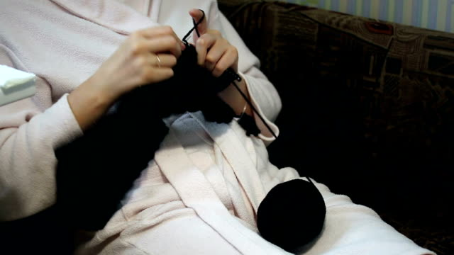 A woman in a housecoat engaged in knitting. video
