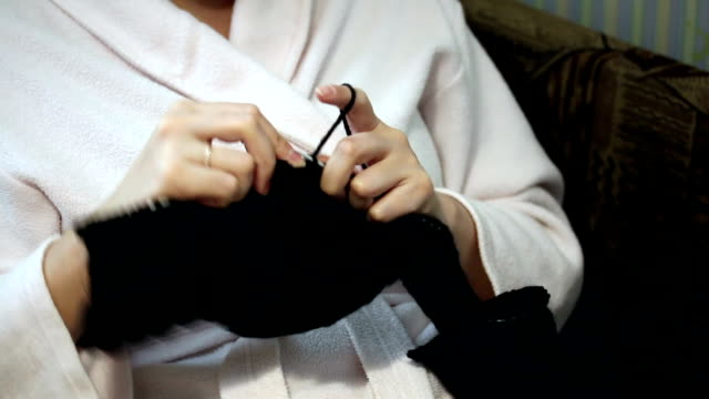 A woman in a housecoat engaged in knitting video