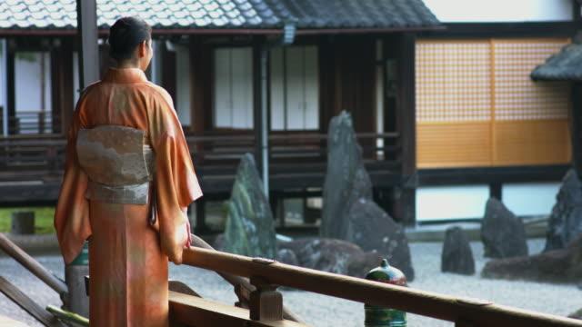 vídeos de stock, filmes e b-roll de mulher de quimono ficou olhando um jardim de rocha - templo