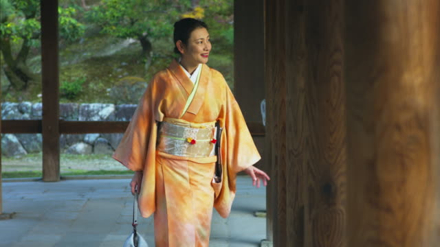 Woman in a kimono stood pensively in a Japanese temple video