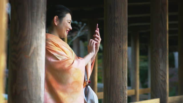 Woman in a kimono taking a photo using her cell phone video