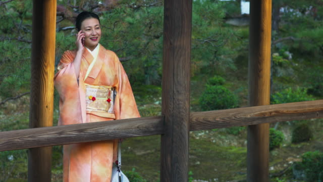 Woman in a kimono talking on the phone video