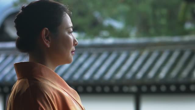 Woman in a kimono walking through a temple corridor video