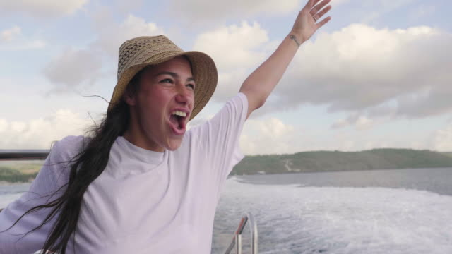 vídeos de stock e filmes b-roll de a woman in a luxury boat has fun, laughs, screams while sailing in the open sea in the summer during her vacation. - enjoying wealthy life