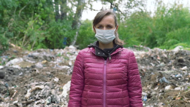 Woman in a Mask Standing Near the Garbage Pile