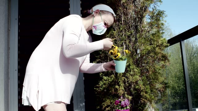 Woman in a mask taking care of plants. Slow motion