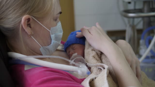 A woman in a medical mask is holding a newborn baby