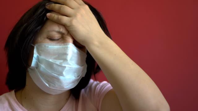 kvinna i en medicinsk mask i ansiktet. huvudvärk - face mask bildbanksvideor och videomaterial från bakom kulisserna
