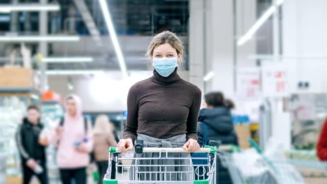 eine frau in einer medizinischen maske steht in einem supermarkt mit einem lebensmittelwagen, zeitraffer. schutz vor coronavirus, lebensmittelkauf in einer krise. - supermarkt einkäufe stock-videos und b-roll-filmmaterial