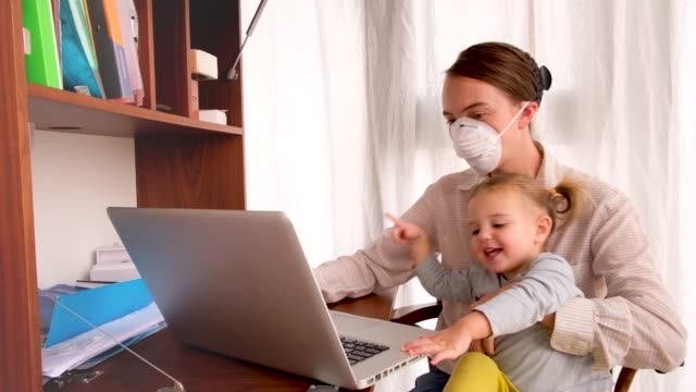 의료 용 마스크를 쓴 여성이 집에서 일하려고 합니다. - 짜증 스톡 비디오 및 b-롤 화면