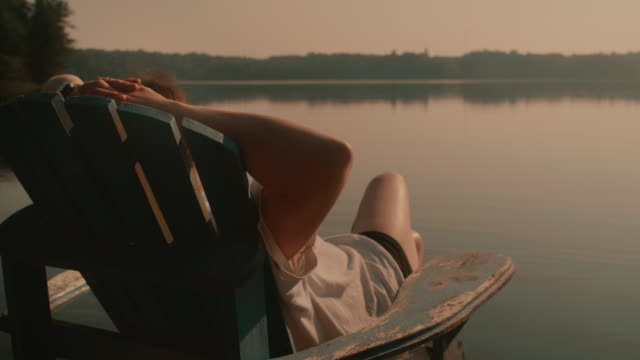 woman in a muskoka chair staring out a lake in cottage country - jezioro filmów i materiałów b-roll
