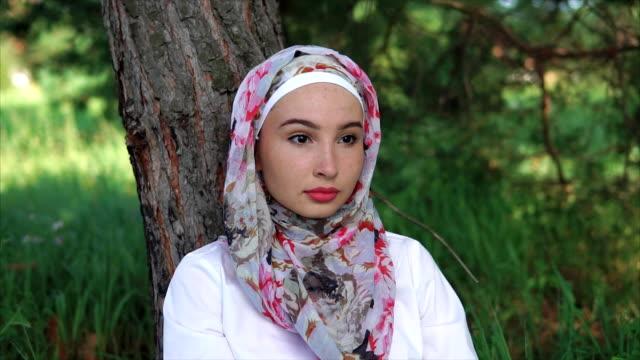 en kvinna i en muslimsk huvudduk som sitter på gräset nära ett träd i parken - anständig klädsel bildbanksvideor och videomaterial från bakom kulisserna